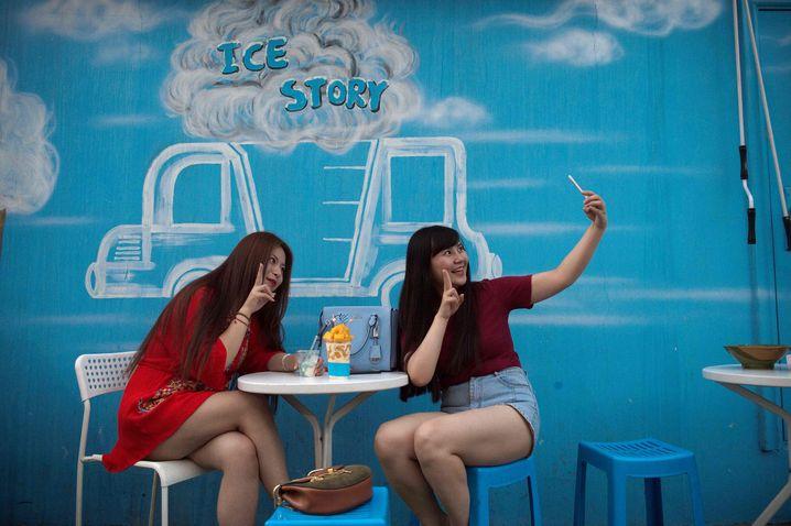 Chinesinnen machen Selfie in einem Pekinger Cafe