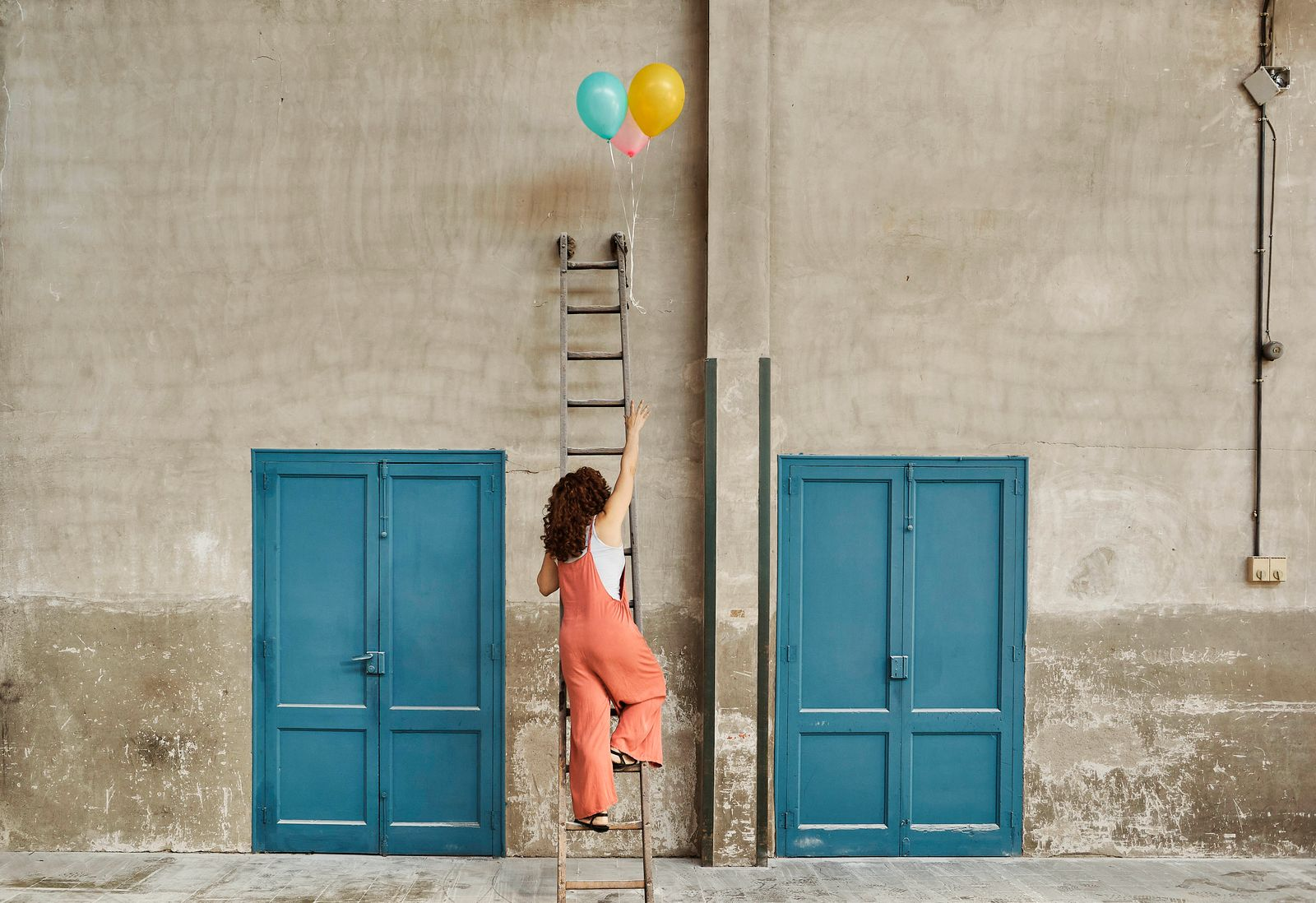 Woman climbing ladder leaning on wall while reaching for colorful helium balloons model released Symbolfoto property rel