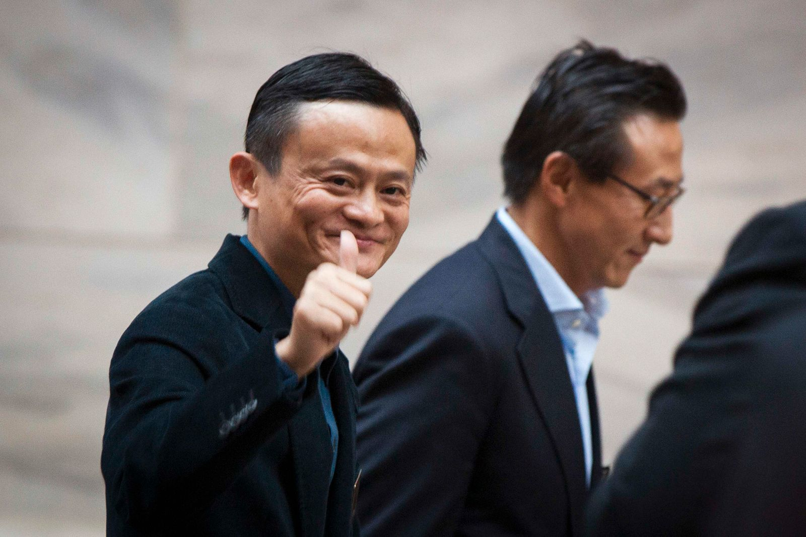 """Alibaba Group Holding Ltd founder Jack Ma gestures in front of the New York Stock Exchange before his company's initial public offering (IPO) under the ticker """"BABA"""" in New York"""