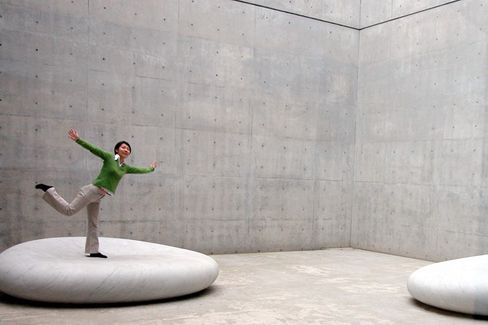 Kunst zum Erleben: Eine Besucherin posiert auf einer Steinskulptur von Yasuda Kan