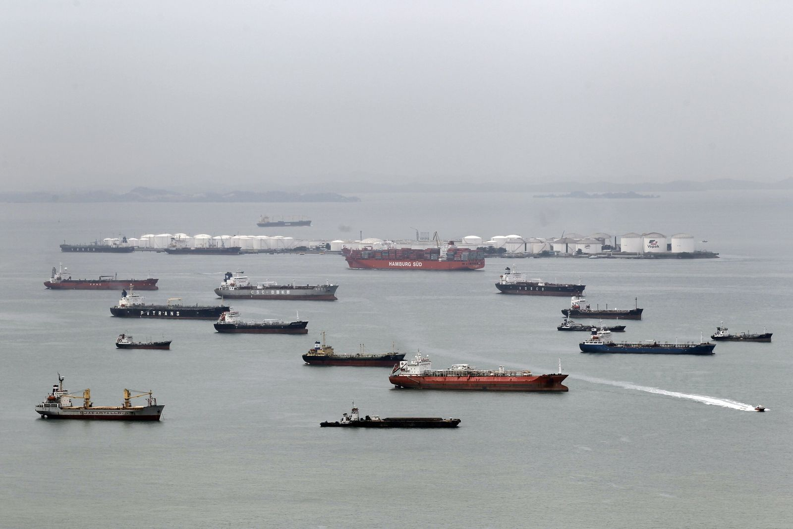 The container ship Hamburg Sud (C) steams out of port past bulk c