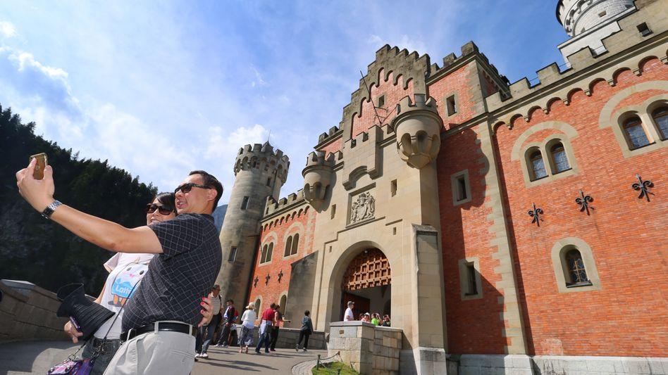 Touristen aus Asien fotografieren sich vor dem Schloss Neuschwanstein. Gruppenreisen sind für Chinesen definitiv out.