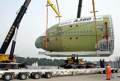 Die erste Reise geht übers Wasser: Airbus-Mitarbeiter verladen in Hamburg-Finkenwerder die Cockpitsektion des neuen Airbus A380 auf ein Binnenschiff