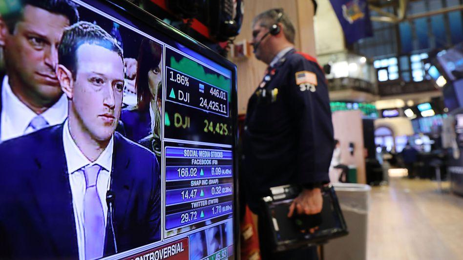 Zuckerberg im Fernsehen, verfolgt von Händlern der Börse in New York: Die Ämterhäufung des Facebook-Chefs gefällt nicht allen Investoren.