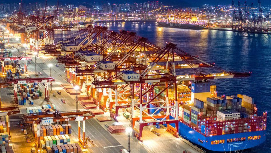 Containerschiffe im nächtlich beleuchteten Containerterminal des Hafens von Qingdao