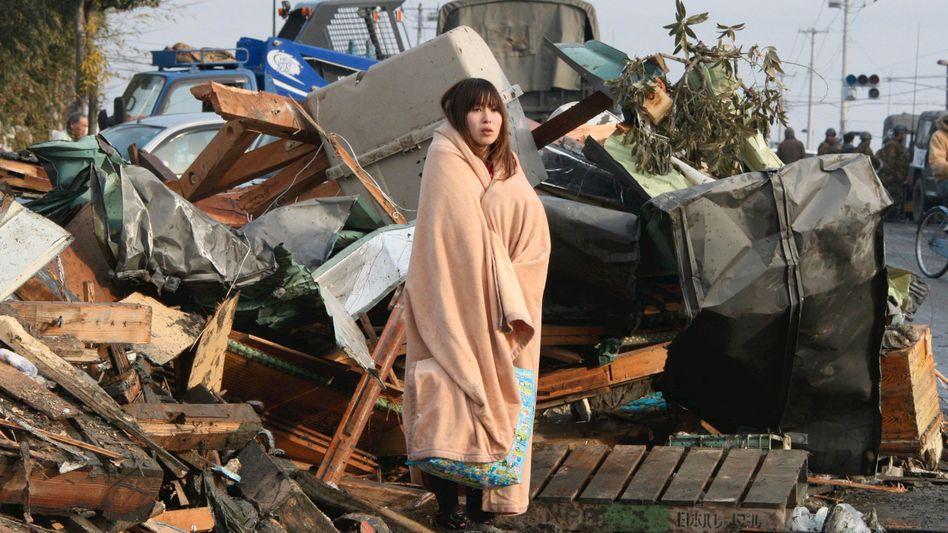 Verwüstungen: Eine Frau wartet in der verwüsteten Stadt Ishimaki auf Hilfe