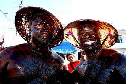 Schlamm und Öl auf der Haut: Nach den Straßenumzügen müssen die Karnevalsfans auf Trinidad unter die Dusche