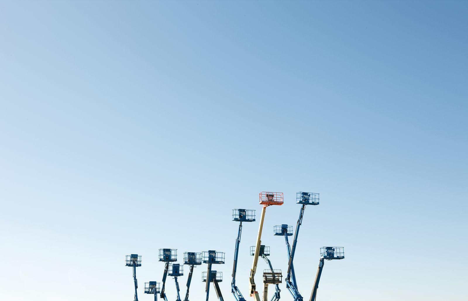 Cherry picker platforms raised against sky