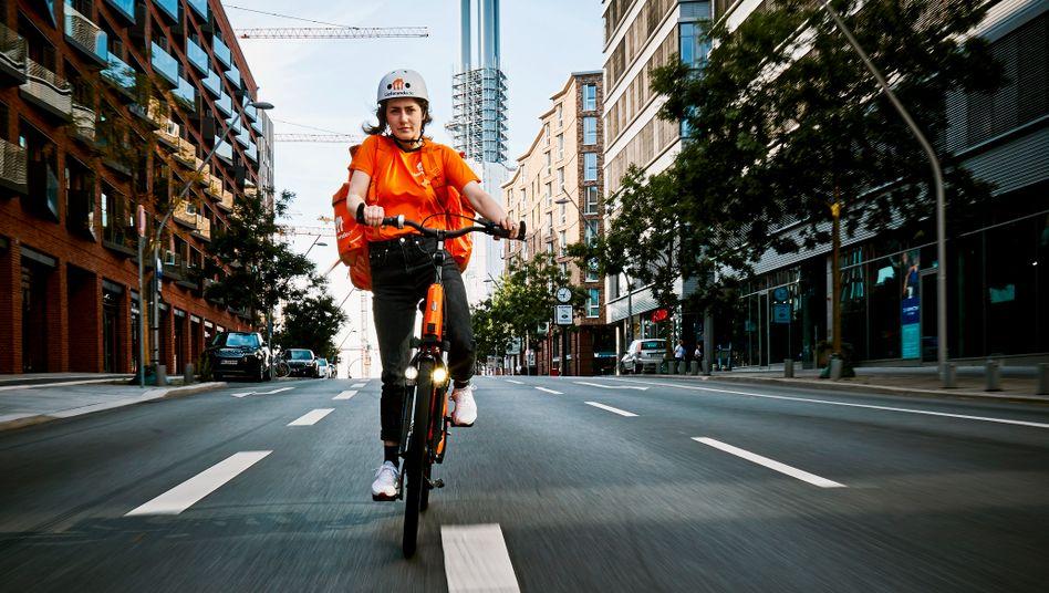 Lieferando-Fahrerin in Hamburg: Die Auslieferung mit eigenen Kurieren ist für die Lieferdienste ein Verlustgeschäft.