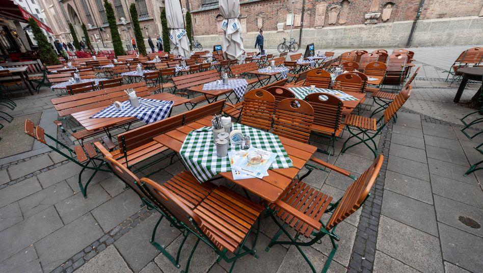 München: Leere gedeckte Tische stehen um die Mittagszeit vor einem Restaurant nahe der Frauenkirche
