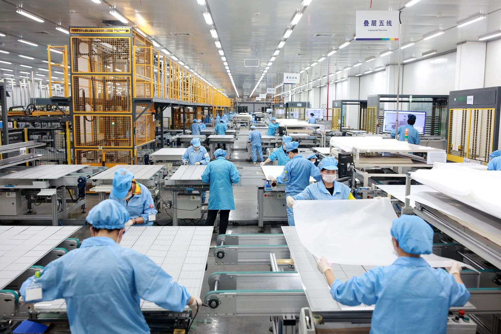 Employees work on photovoltaic solar panels at a factory of Risen Energy in Ningbo