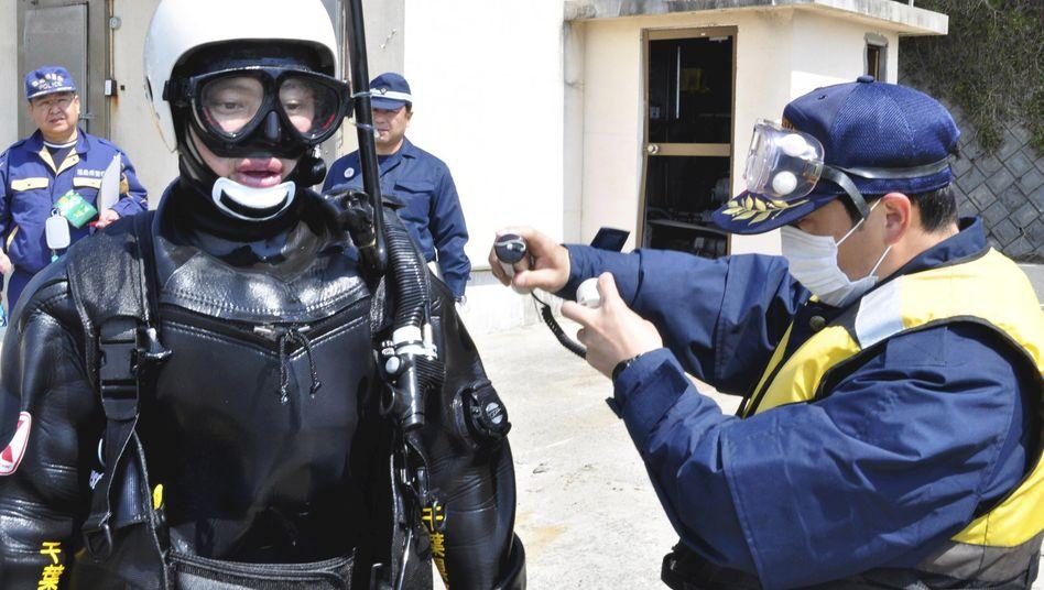 Atomkatastrophe in Japan: Mit einem Geigerzähler wird der Taucher auf Radioaktivität untersucht