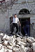 Ein bewaffneter Palästinenser vor der zerstörten Polizeistation in Ramallah