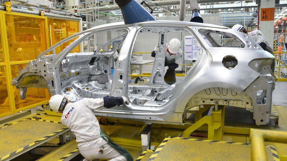 Interesse des Partner aus China: Arbeiter in einer Fabrik von PSA Peugeot Citroen im südchinesischen Shenzhen