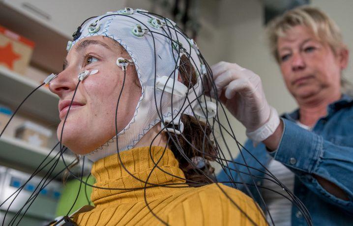 Magdeburg: Die medizintechnische Assistentin Gabi Schöns richtet eine Haube mit Elektroden zur Messung der Hirnströme im Labor für Neurobiologie am Leibniz-Institut bei einer Probandin ein.