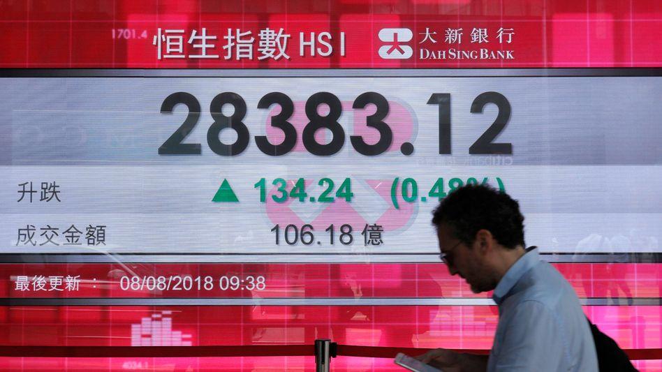 China, Hong Kong: Ein Mann geht an der Anzeige einer Bank vorbei, die den Aktienindex von Hongkong an der Hong Kong Stock Exchange zeigt