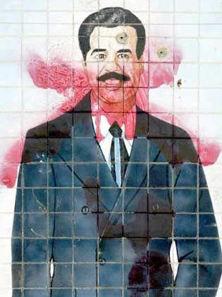Ein Bild von Saddam Husseein mit roter Farbe beschmiert