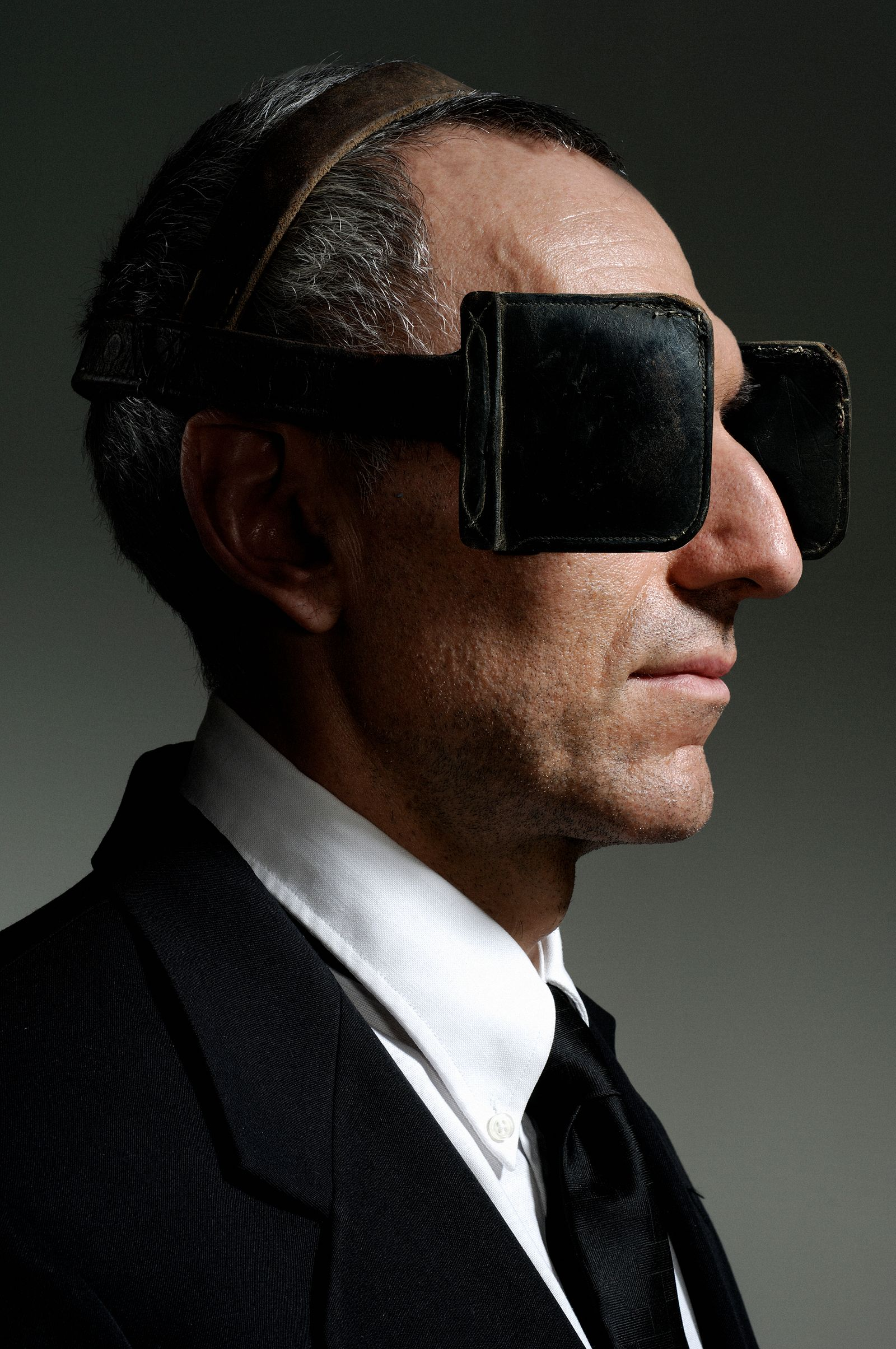 Mature businessman wearing blinkers, close-up, side view