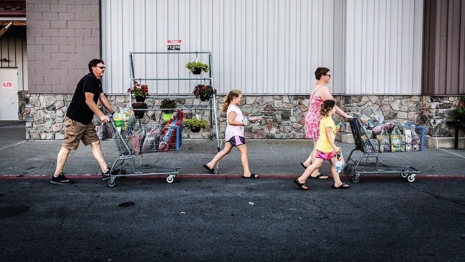 Once Upon a Time: Eine Familie in Fulton, New York, schiebt den Einkauf bei Walmart zum Auto.