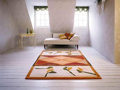 Farbtupfer von Vorwerk: Ein gemusterter Teppich in Erdtönen und floralem Dekor ziert einen schlichten weißen Raum