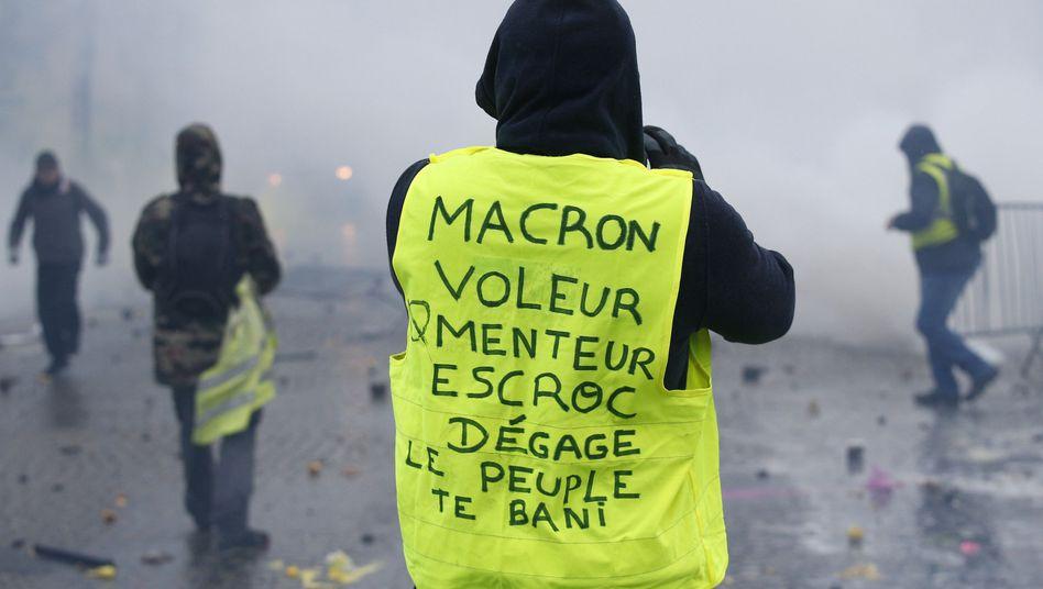 """Ein Demonstrant trägt eine Warnweste auf der zu lesen ist """"Macron, Dieb, Lügner, Gauner, verschwinde, das Volk verbannt dich"""". Nach tagelangen teils gewalttätigen Protesten gegen höhere Steuern auf Energie legt Frankreichs Regierung die Pläne vorerst auf Eis."""