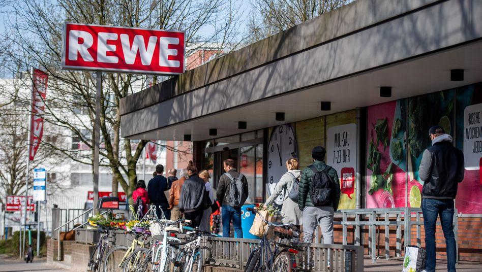 Typisches Bild in Corona-Zeiten: Wartende Kunden vor einem Rewe-Supermarkt