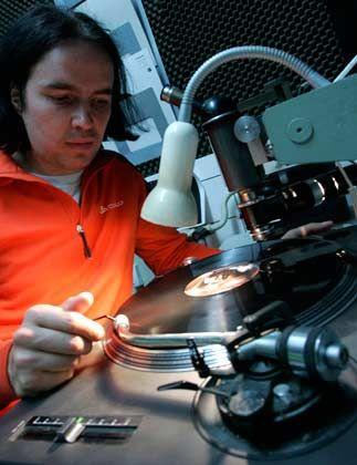 Traditionelle Kunstform: 25 Sekunden benötigt eine mit einer Nickel-Matritze bestückte Presse, um aus einer Ladung schwarzer Vinylkügelchen eine Schallplatte zu pressen