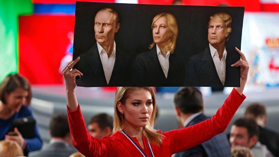 Die drei ... - was eigentlich? Eine Besucherin der jährlichen Pressekonferenz des russischen Präsidenten Wladimir Putin hält am 23. Dezember ein Schild in die Höhe.