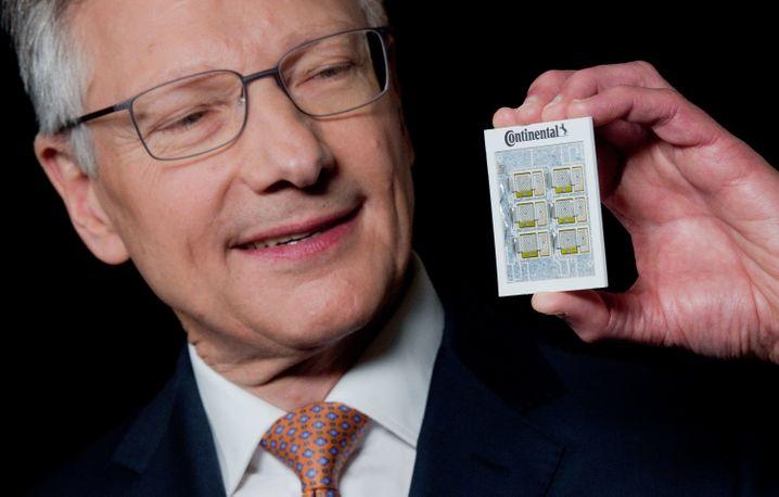 """Continental-Chef Elmar Degenhart zeigt eine Platine aus der Leistungselektronik für Elektrofahrzeuge - laut Conti das """"Herz und Hirn"""" des Elektroautos der Zukunft"""