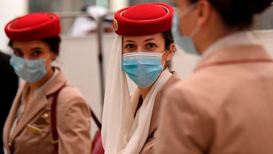 Nur noch mit Mundschutz: Stewardessen der Airline Emirates kommen von einem Flug von London in Dubai an. Noch ist der Himmel nicht für massenhafte reguläre Passagierflüge geöffnet.