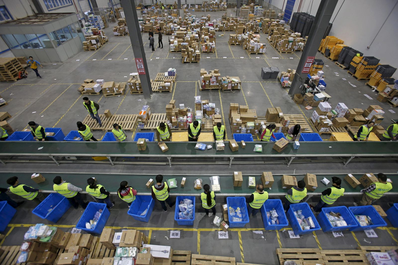 Employees sort boxes and parcels next to a conveyor belt at the logistic centre of a express delivery company, after the Singles Day online shopping festival, in Wuhan
