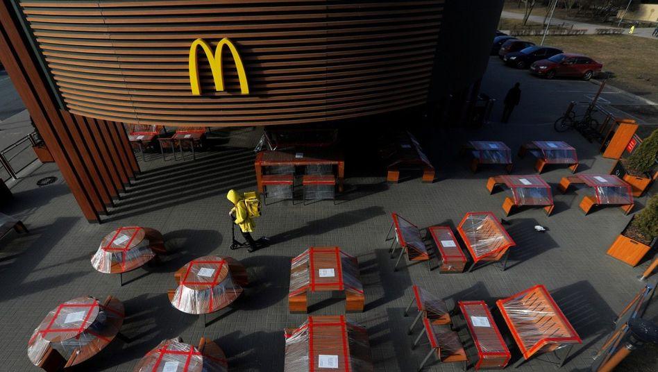 Tischlein, verdeck dich:Das Zukunftsbild, wenn auch unfreiwillig: Die Sitzgelegenheiten dieses McDonald's in Sankt Petersburg sind eingemottet, der Lieferdienst (in Gelb) macht sich auf den Weg.