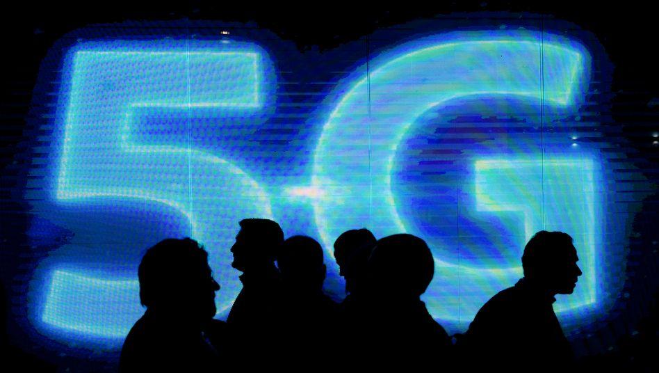Besucher vor einem 5G-Logo auf dem Mobile World Congress in Barcelona