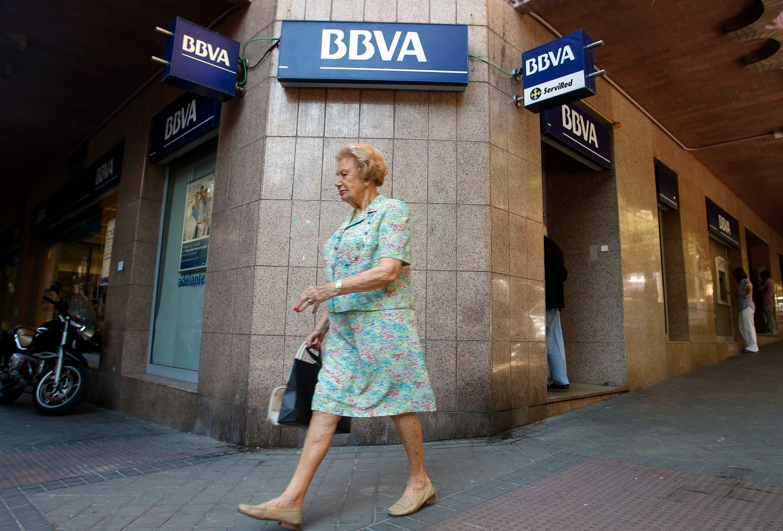 Woman walks past a BBVA bank in downtown Madrid
