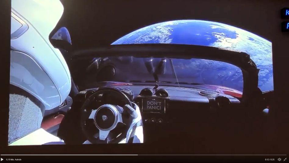 Don´t Panic: Während ein roter Tesla durch das All schwebt, arbeitet Elon Musk unten auf der Erde an den Produktionsproblemen des Model 3