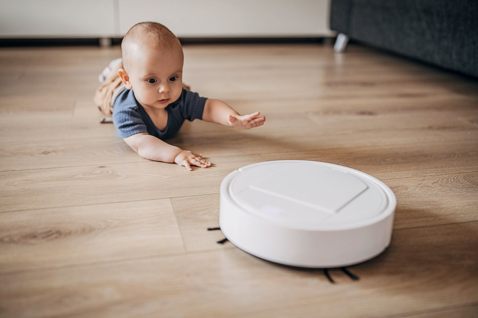 Baby boy discovering robotic vaccum cleaner