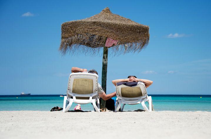Sand, Meer, Sonne: Mehr wollen viele Urlauber gar nicht. Hier ein Paar am Strand der Platja de Muro im Norden Mallorcas.