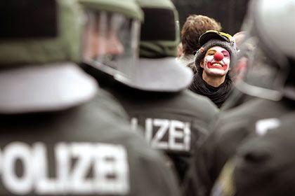 Rostock: Eine als Clown verkleidete G8-Demonstrantin protestiert gegen gegen Gipfel in Heiligendamm - hinter einer Polizeikette