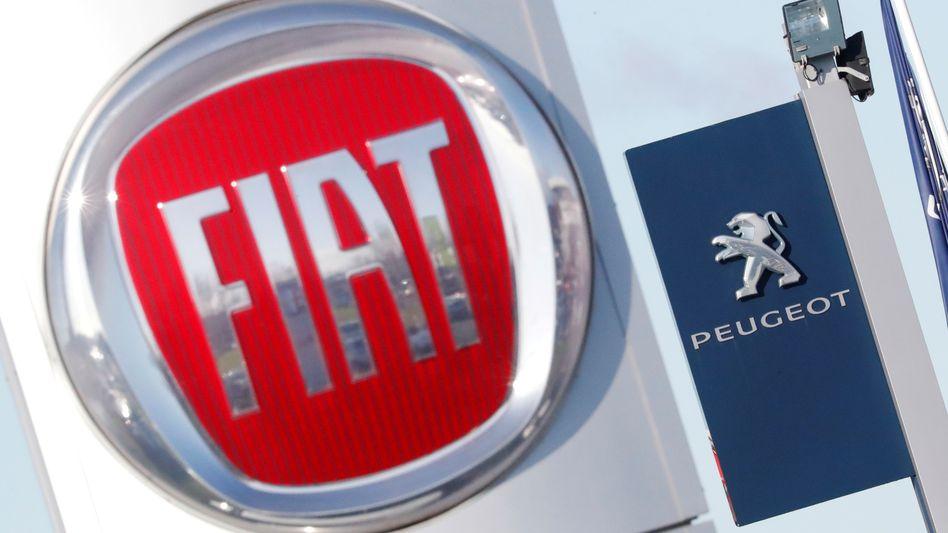 Aus zwei mach eins: Logos von Fiat und Peugeot vor einem Autohaus in Saint-Nazaire