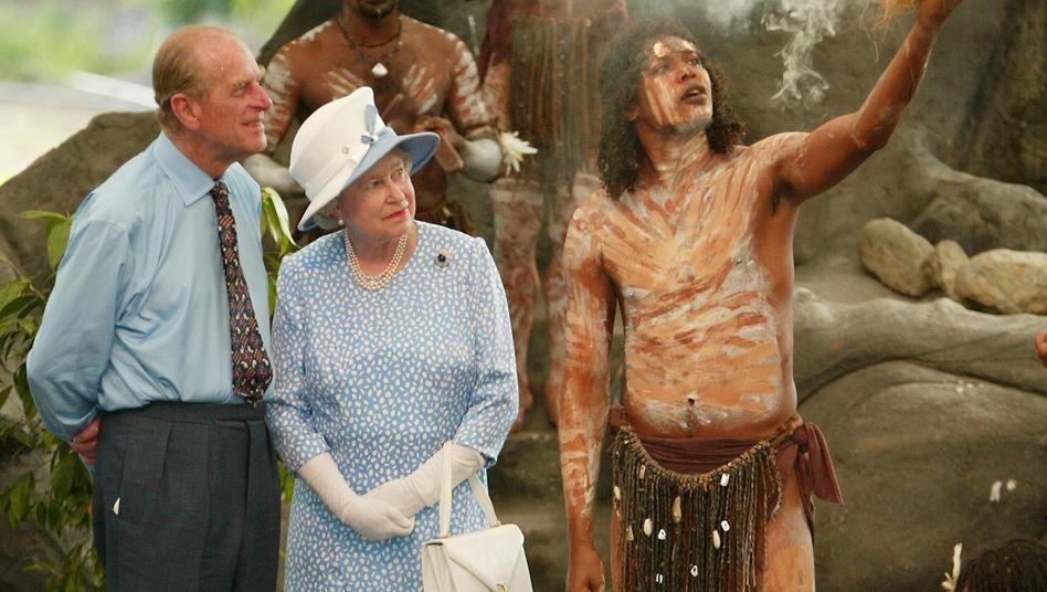 """Andere Länder, andere Sitten: Königinnengemahl Prinz Philip (links) gilt als König der Fettnäpfen und hat sich im Ausland immer wieder in die Nesseln gesetzt. Einen australischen Ureinwohner fragte er einmal interessiert: """"Werfen Sie immer noch mit Speeren aufeinander?"""""""