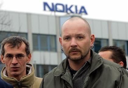 Betroffene Gesichter: Mitarbeiter stehen am Dienstag vor dem Eingang des Nokia-Werks in Bochum.