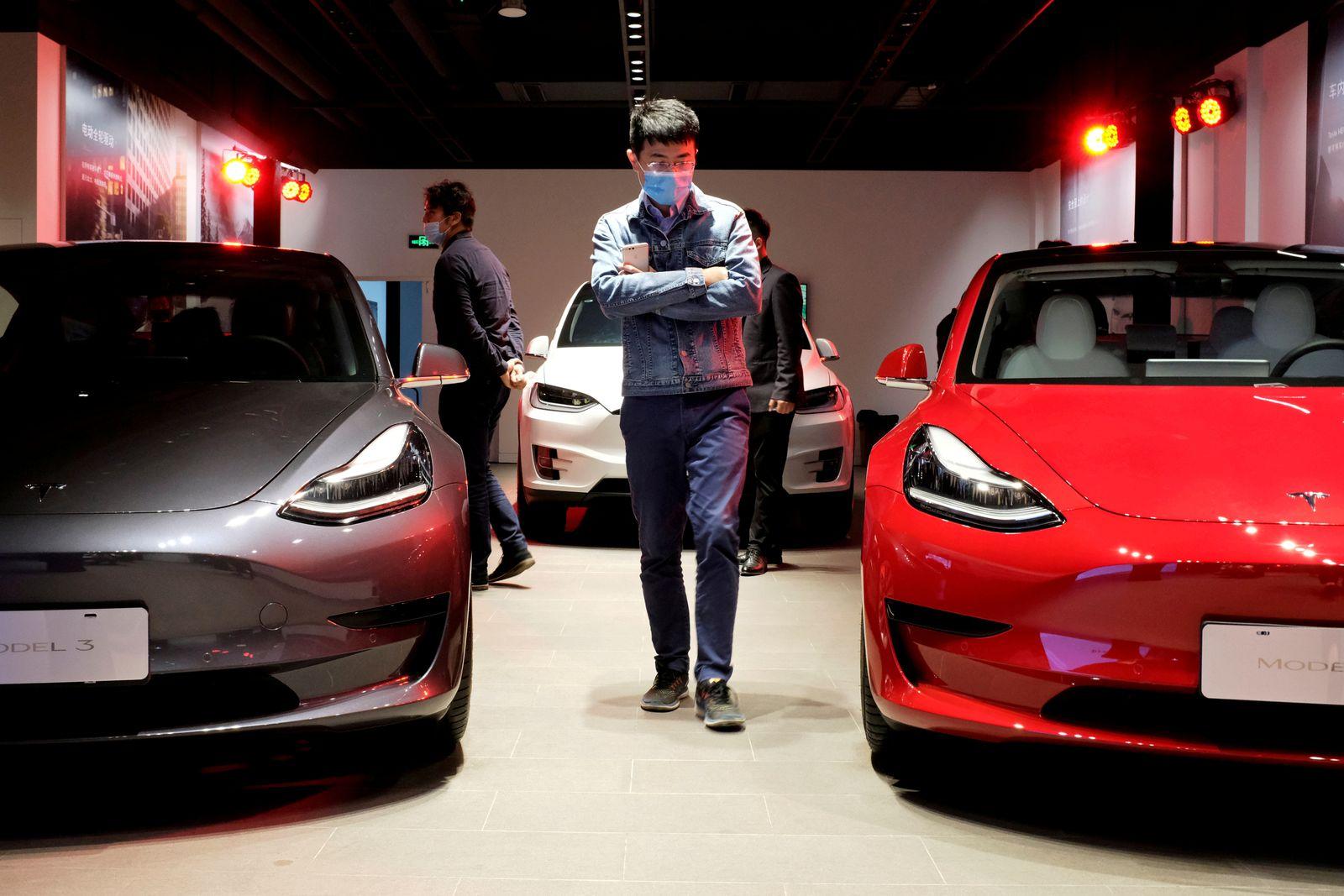 FILE PHOTO: Man walks by Tesla Model 3 sedans and Tesla Model X sport utility vehicle at a new Tesla showroom in Shanghai
