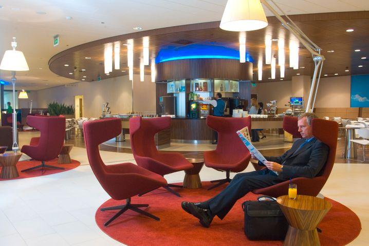 Mit einer gut sortierten Bar im Hintergrund (hier eine KLM-Lounge) ist das Warten am Flughafen gleich etwas erträglicher