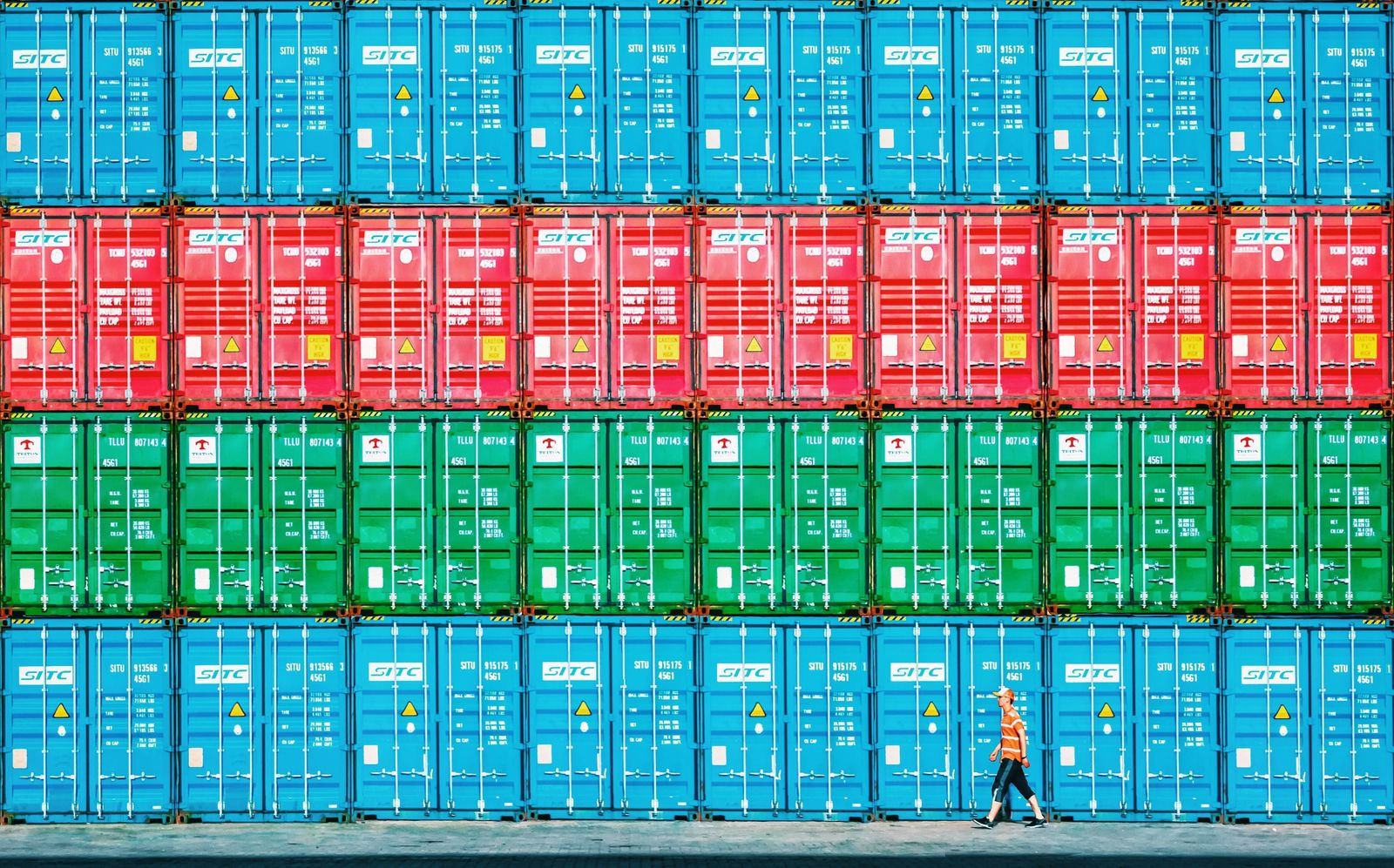 LIANYUNGANG, CHINA - AUGUST 09: A worker walks by piled-up containers at Port of Lianyungang on August 8, 2019 in Liany