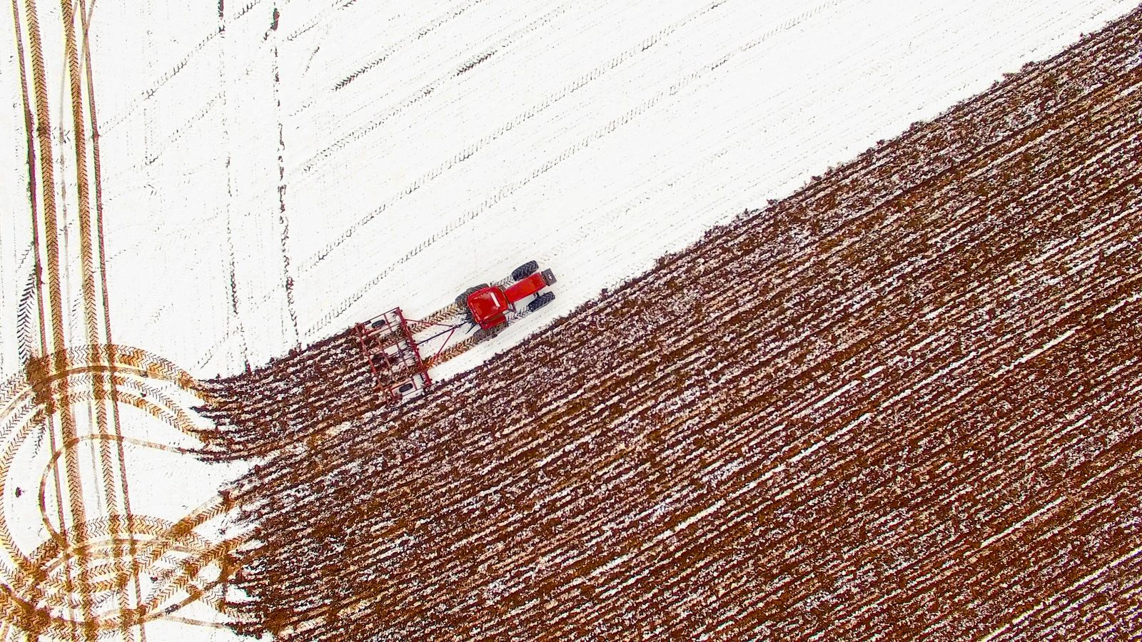 Aerial view of tractor tilling snow covered field in Winter.