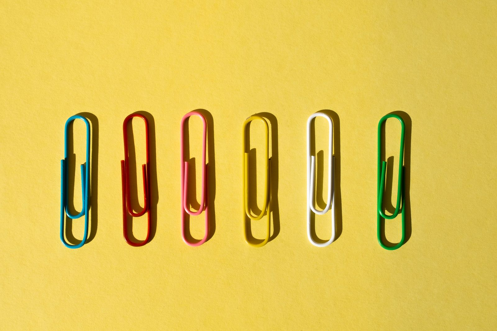 Colorful Paperclips on the yellow background