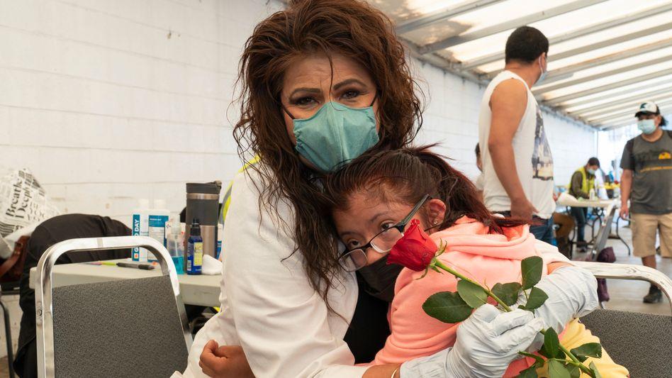 Es ist überstanden: Eine Krankenschwester umarmt die am Down-Syndrom erkrankte Guadalupe Zamarripa nach der Impfung mit Biontech - die USA haben jetzt den Corona-Impfstoff für Kinder und Jugendliche freigegeben