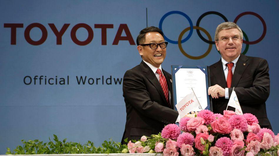 Klatsche vom wichtigsten Sponsor: Einst trommelte Toyota-Chef Akio Toyoda (l.) gemeinsam mit IOC-Chef Thomas Bach (r.) für die Olympischen Spiele in Tokio - nun bleibt Toyota aus Image-Bedenken der Eröffnungszeremonie fern