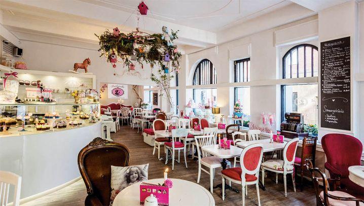 Café Barbarella in der Pontstraße: auf pinken Stühlen, zu Kronleuchter und Törtchenvitrine