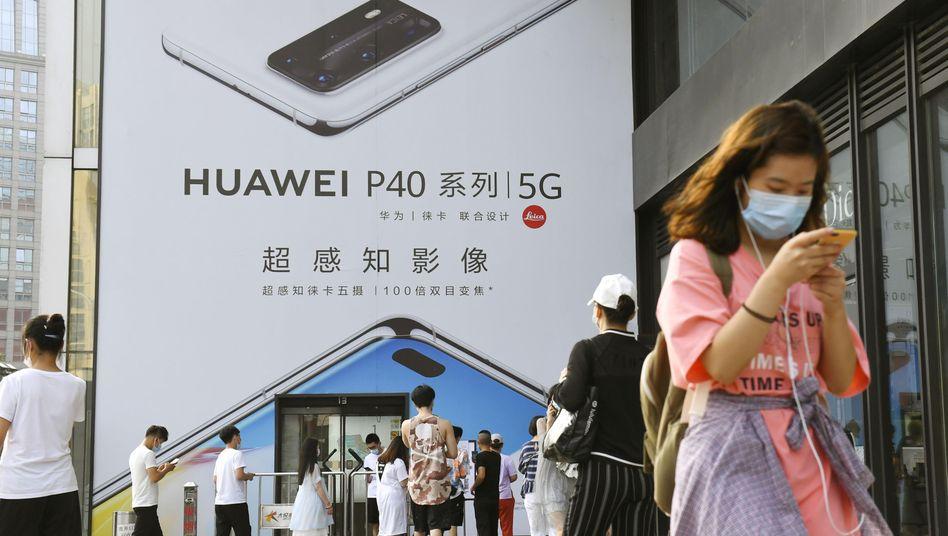 Passanten in Peking vor einem Huawei-Geschäft